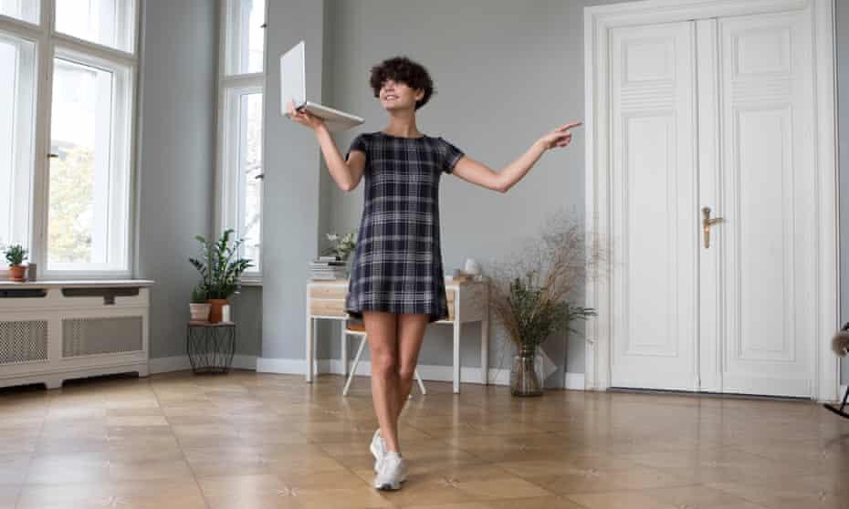 Woman dancing holding laptop
