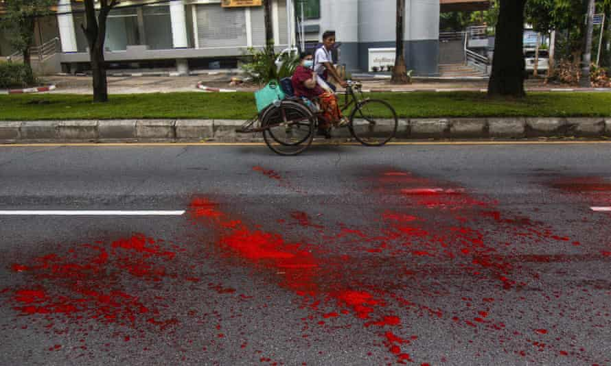 A rickshaw passes by a street with splashes of red paint, a 'blood strike', sprayed by anti-coup protesters during a demonstration in Yangon.