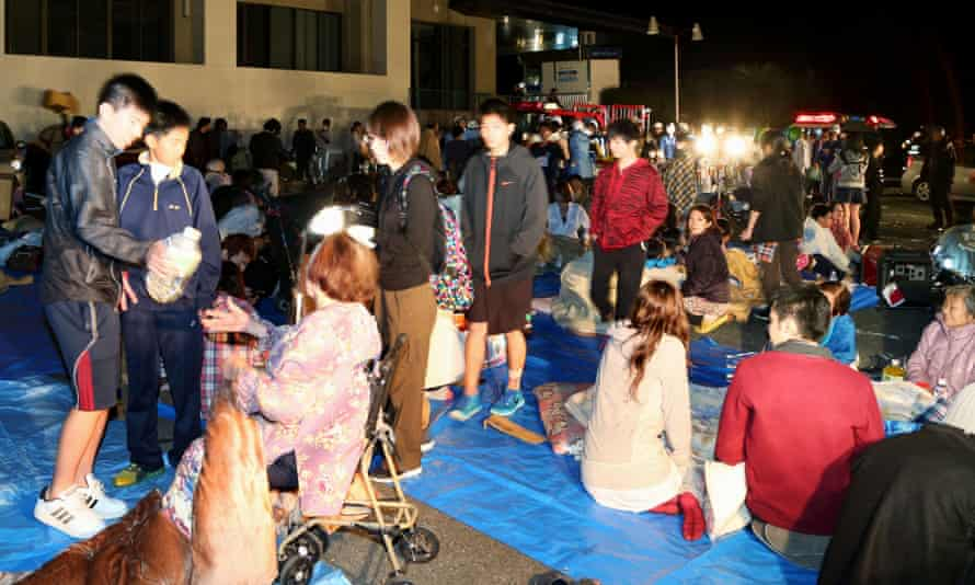 Stranded people gather outside a town hall in Mashiki.