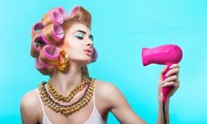 Glamorous woman blow drying her hair