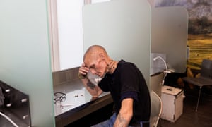A drug user after injecting heroin in his arm at 'The Cloud' fixing room facility in Copenhagen, Denmark.