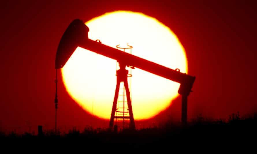 The sun sets behind an oil pump