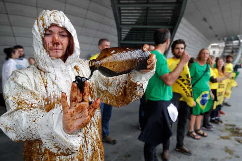 A climate activist pours oil on her hands during a demonstration outside the Palais des Congrès, Paris, after environmentalists disrupted Total's annual shareholders meeting in protest against its plan to the drill in the Amazon basin.