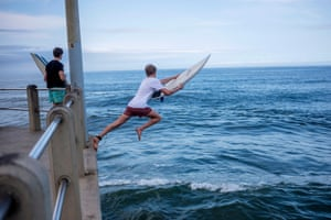 A surfer jumps into the ocean from a pier at Durban's North Beach