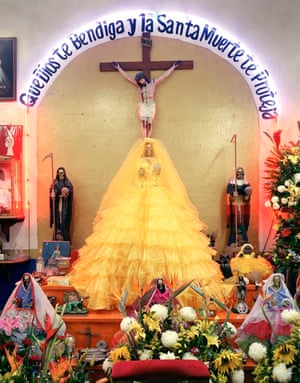 A Shrine in Puebla, Puebla State, Mexico. Santa Muerte icons are dressed in different colours to symbolise different tasks, here gold represents a need for economic and financial success.