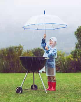 Boy barbecuing in the rain