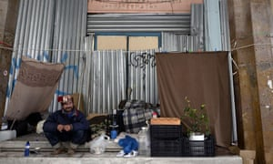 A homeless man sits the former education ministry in Athens