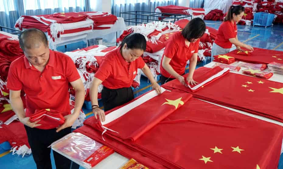Workers make flags at a factory in Wuyi, Zhejiang, ahead of national day. The country's economy is showing signs of slowing down.