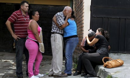 Relatives of Josue David Penalba Rivera react as police secure a crime scene in San Salvador on 1 June 2015. Rivera was shot by suspected gang members.