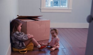 Little brown haired girl sitting on a suitcase in an empty room with one box and staring at her doll<br>A05HB3 Little brown haired girl sitting on a suitcase in an empty room with one box and staring at her doll