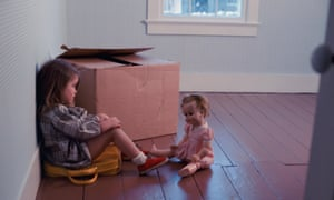 girl sitting on a suitcase in an empty room