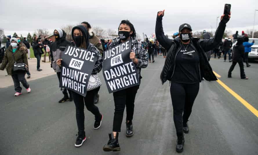 Protesters carrying 'Justice for Daunte Wright' signs march near the Brooklyn Center police department in Minnesota on 13 April.