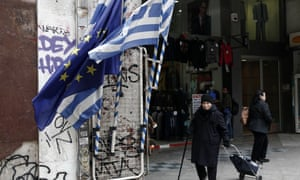 A woman pulls a shopping trolley next to a Greek and an EU flag in Athens