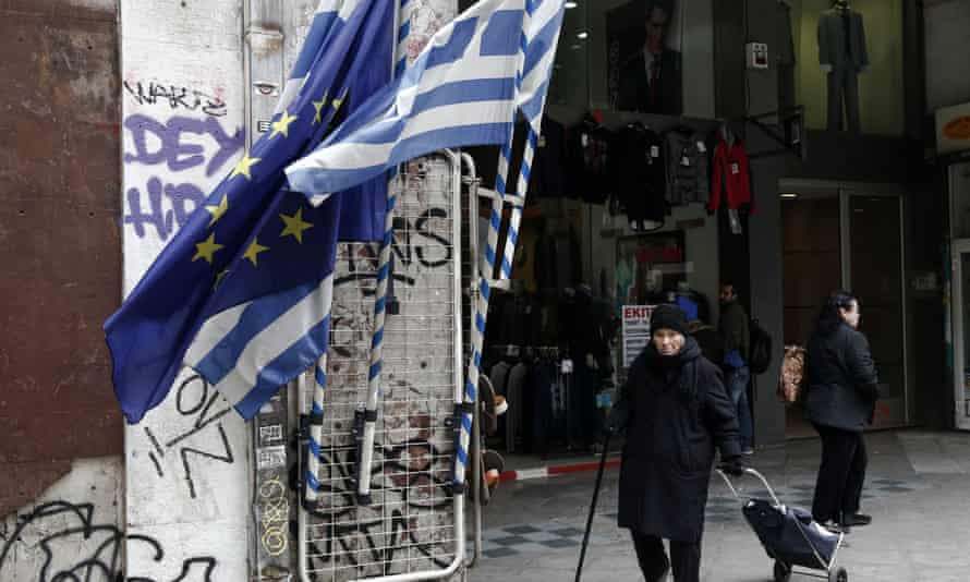 A woman pulls a shopping trolley past EU and Greek flags in Athens