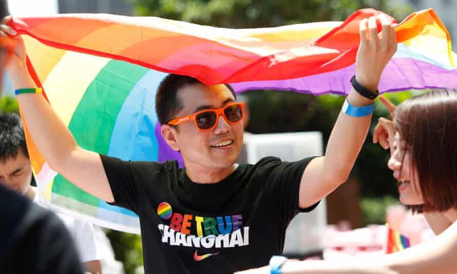 A man holds a rainbow flag in Shanghai.
