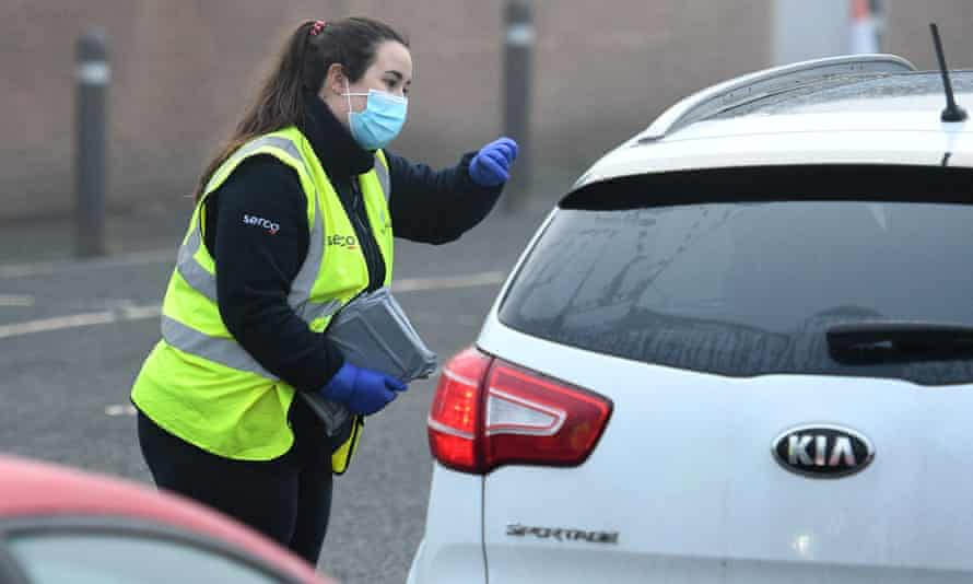 A Serco worker passes coronavirus test kits to members of the public arriving at a temporary facility in Walsall.
