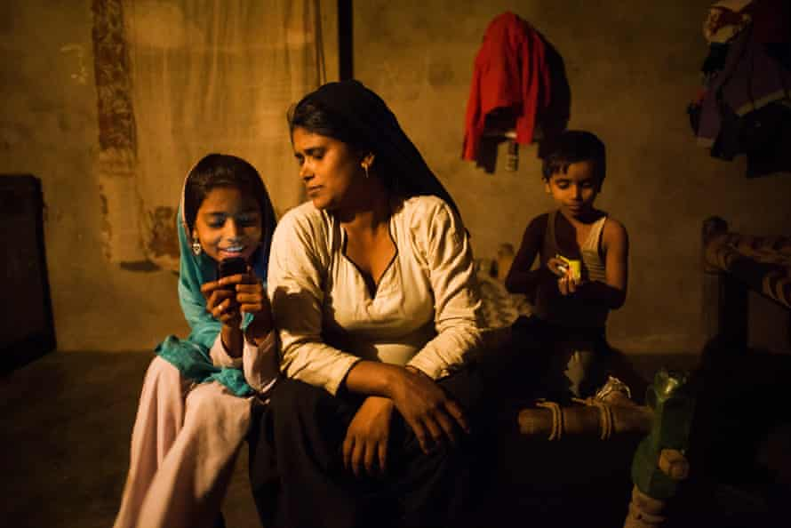 Sanjida* with two of her four children in their home in the Mewat district of Haryana