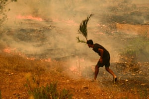 Manavgat, Turkey: A man tries to extinguish bushes during a forest fire which engulfed a Mediterranean resort region on Turkey's southern coast