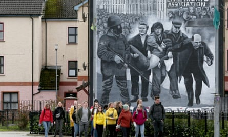 Tourists on a walking tour pass a mural depicting Bloody Sunday.