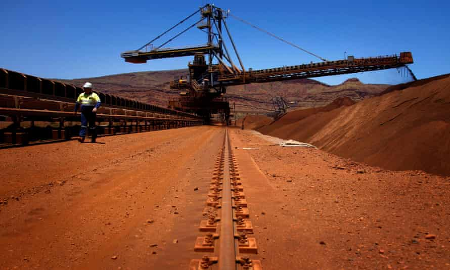 A mine worker inspects conveyer belts transporting iron ore at the Fortescue Solomon iron ore mine in the Pilbara region of Western Australia.