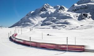 The Bernina Express passing through snowy mountains