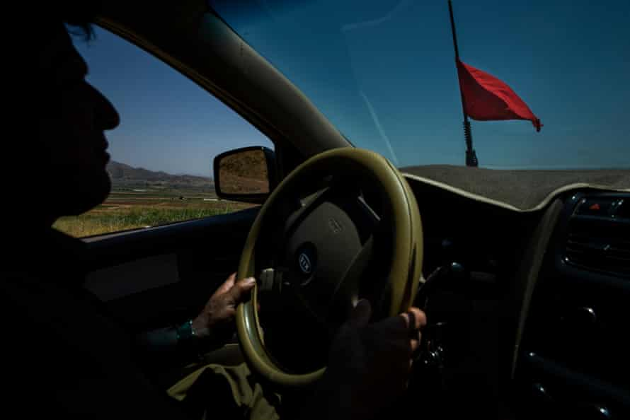 Landmine deminer Hoshyar Ali drives to help a man after receiving a request to help remove landmines from the farmers property near Penjwen, Iraqi Kurdistan. The red flag indicates his vehicle contains explosives.