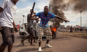 Demonstrators gather in front of a burning car during an opposition rally in Kinshasa that called on the long-serving president, Joseph Kabila, to step down.