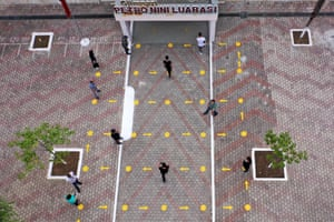 This aerial view shows high school students entering into a school respecting social distancing measures as they return to school.
