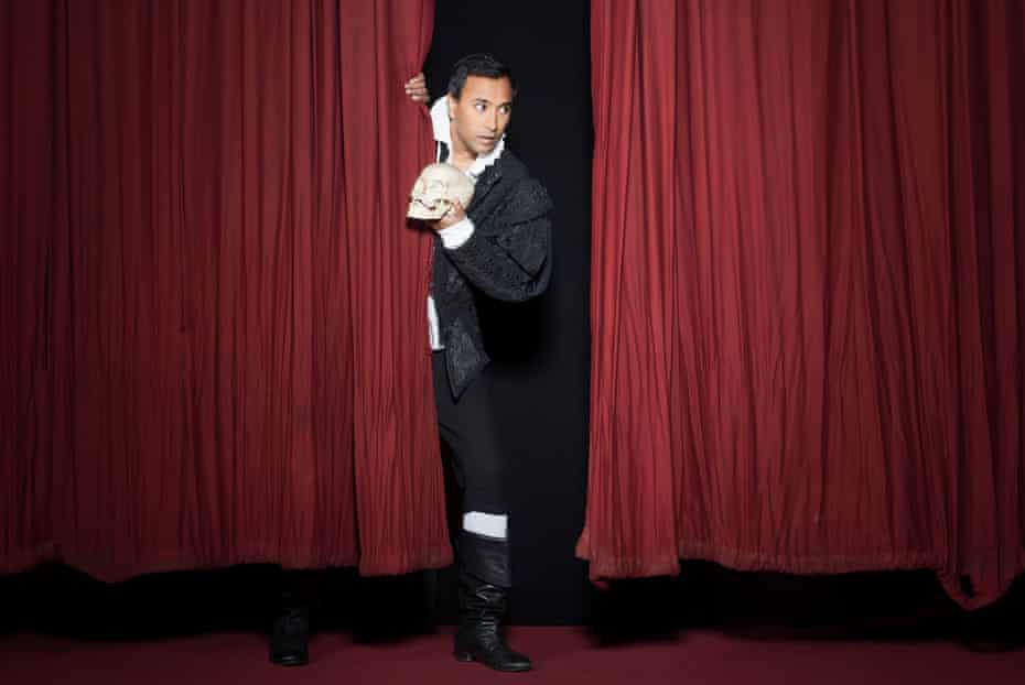 Rhik Samadder holding a skull and looking out from behind red stage curtains