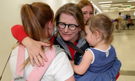 Passengers reunite with family members after arriving at Perth airport on Saturday