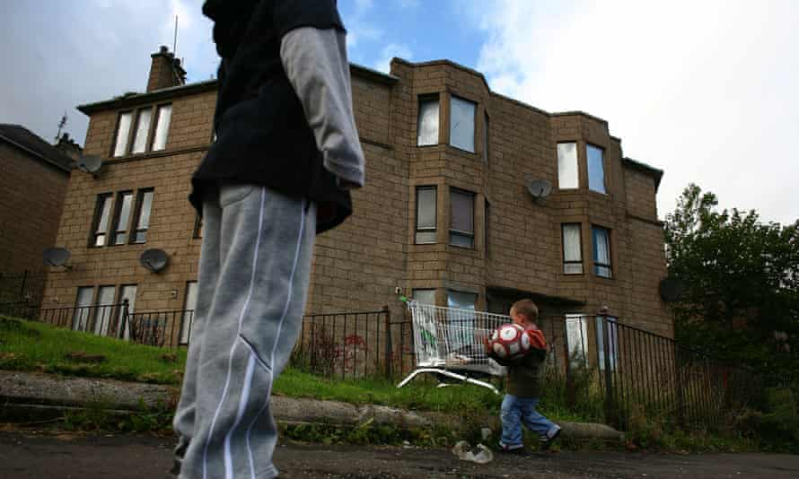Boys play in front of a house with boarded up windows in Scotland