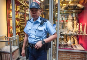 A police officer stands guard outside a shop selling ivory during a protest against Hong Kong's legal ivory trade.