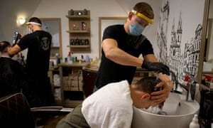 Hairdressers wearing face masks and face shields work in a salon in Prague, the Czech Republic, 11 May