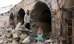 A Syrian man stands among heavily damaged buildings