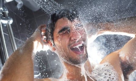 Man in shower, rinsing shampoo from hair (posed by model)