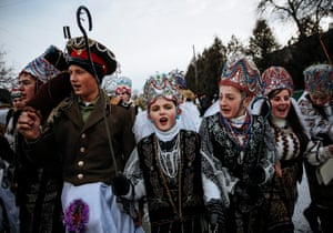 Children in folk costume walk from house to house singing carols