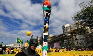 A protester dressed as Batman awaits the torch relay on Copacabana Beach boulevard.