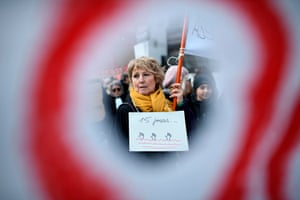 A woman holds a placard reading '15 days' during a protest against French immigration law in Paris, France