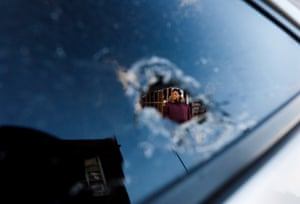 A woman, who did not want to be identified, is seen through a bullet hole in her car's window in front of the kosher market which was the scene this week of a multiple shooting in Jersey City.