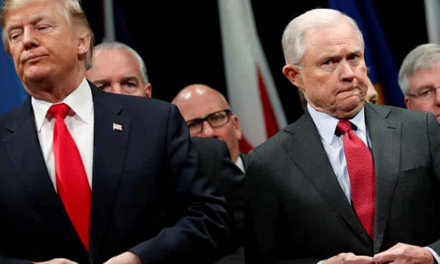 Donald Trump and Jeff Sessions button their coats as they stand for the national anthem at the FBI Academy in Quantico, Virginia in December 2017.