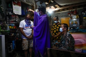 Members of the Espiritu family, who are unable to attend holy mass, receive ashes sprinkled on their head by a priest
