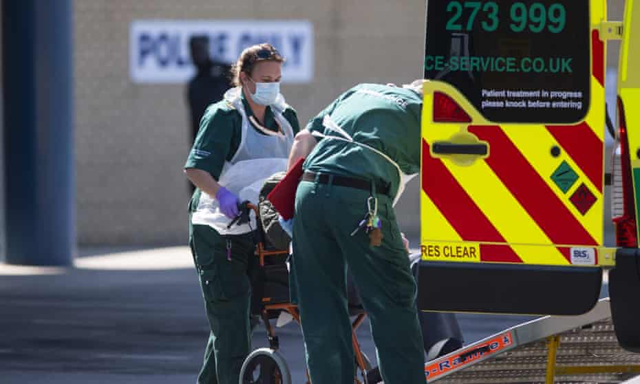 Ambulance staff wearing PPE help a patient out of an ambulance at Queens Hospital in London.
