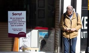 A man waits outside a closed shop on a street corner in Harrogate