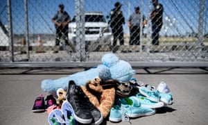 Security personal stand before shoes and toys left at the Tornillo Port of Entry where minors crossing the border without proper papers have been housed after being separated from adults