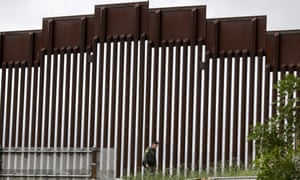 A border patrol agent walks along a border wall separating Tijuana, Mexico, from San Diego, on Wednesday.