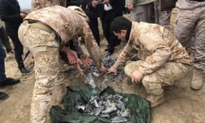 Iraqi security forces collect pieces of missile as they inspect the site after the attack on al-Asad airbase
