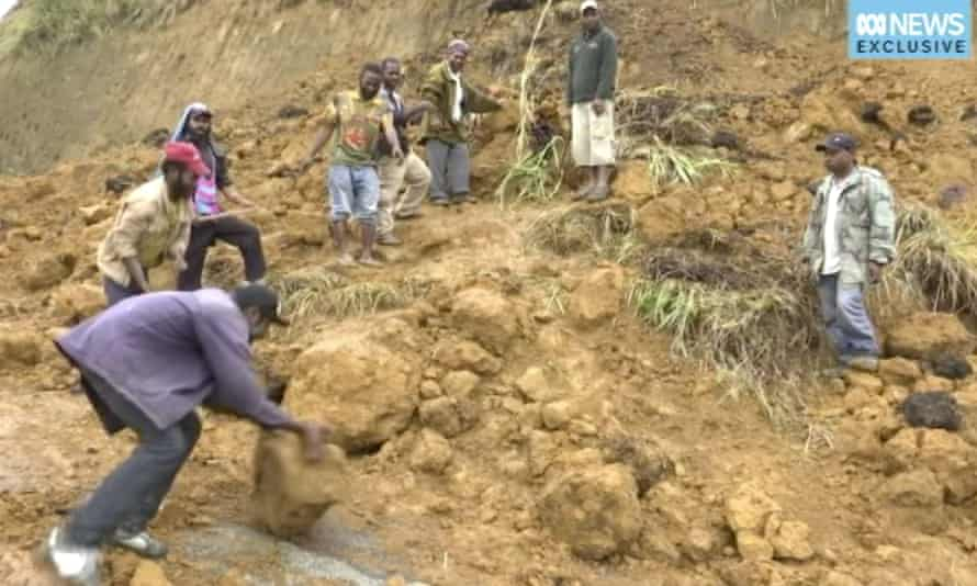 Men struggle to clear a landslide by hand in Hela province.