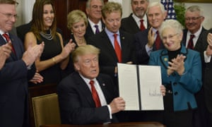 Donald Trump displays an executive order on healthcare after a White House signing ceremony on Thursday.