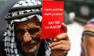 A Palestinian man holds a red card calling for the suspension of Israel's membership in Fifa and say no to racism, during a rally in support of the Palestinian Football Association in the West bank town of Ramallah on 28 May.