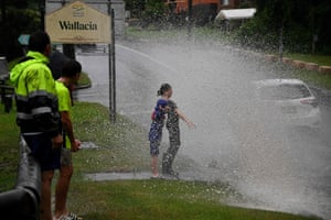 Children getting sprayed with floodwaters from passing motorists near Warragamba Dam